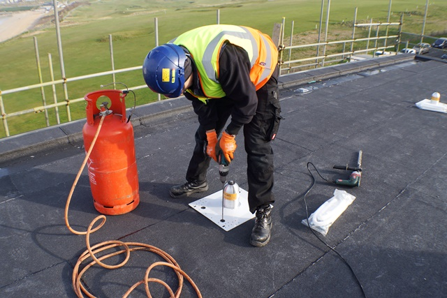 Mansafe Fall protection lifeline systems. Installation of a UK RoofAngel fall restraint system post to a roof membrane.